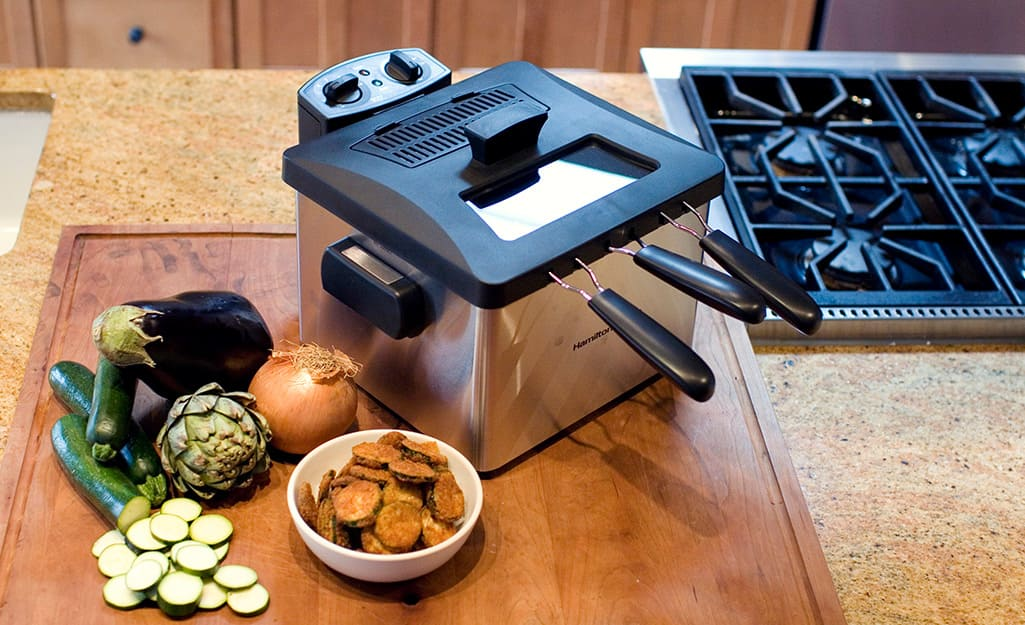 A deep fryer on a wooden cutting board in a kitchen