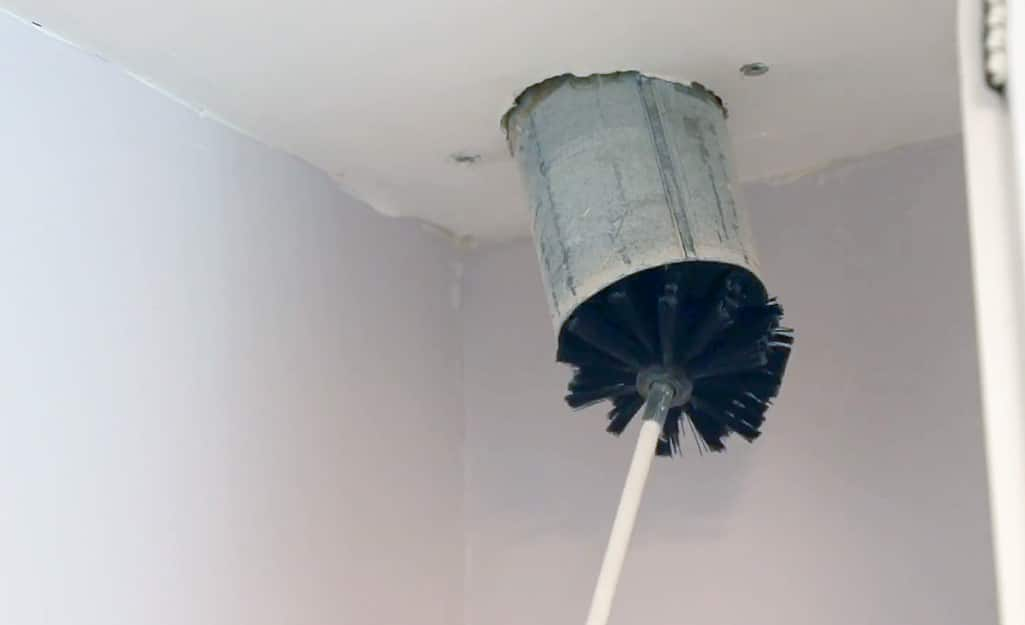 A person uses a flexible brush to clean the inside of a clothes dryer vent.
