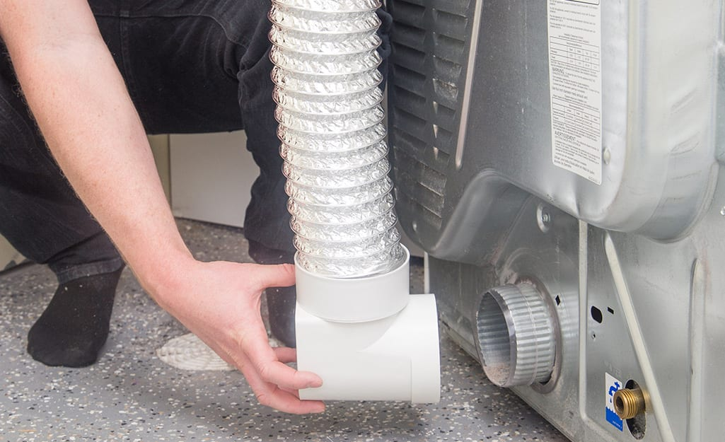 A person reconnects the venting duct to the back of a clothes dryer.