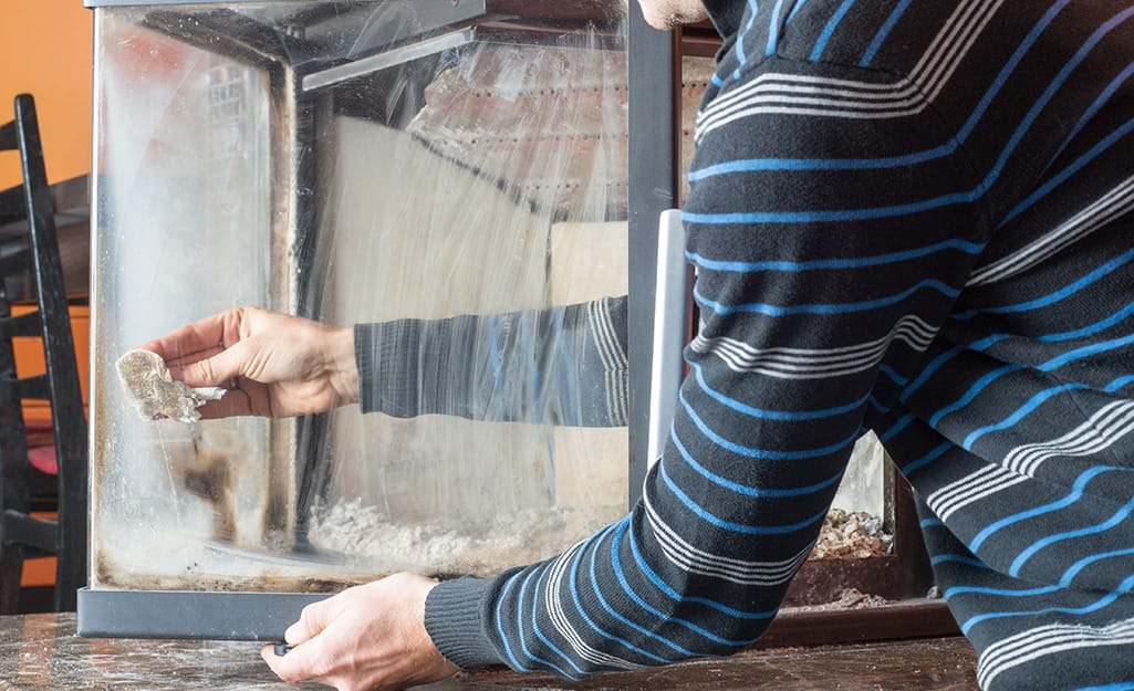 A person cleaning the inside of a glass fireplace screen.