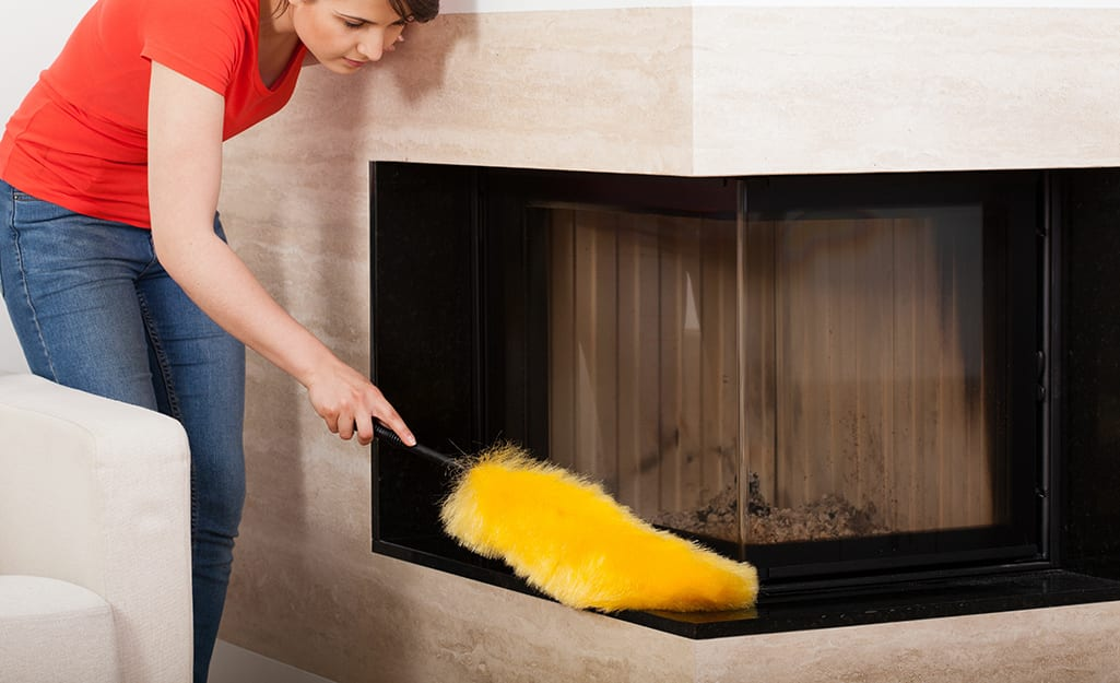 Someone dusting the outside of a fireplace.