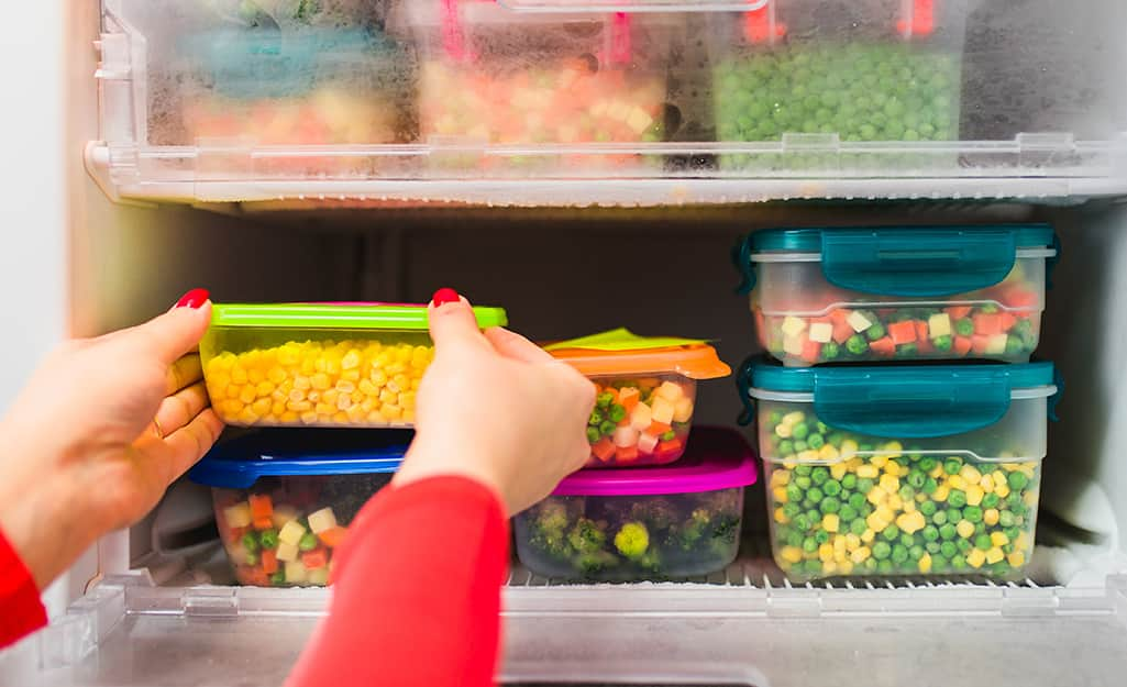 A person checks frozen food in containers for freshness.