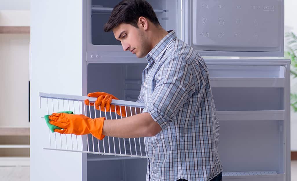 A person wipes a removable shelf from a freezer.
