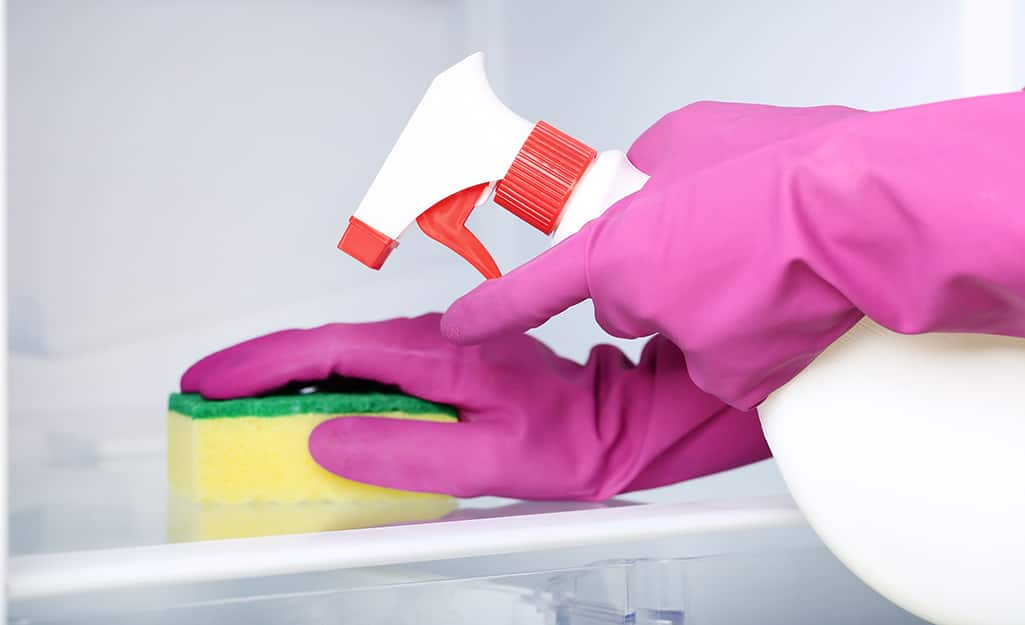 A person wears gloves to clean the inside of a freezer with a sponge and a solution in a spray bottle.