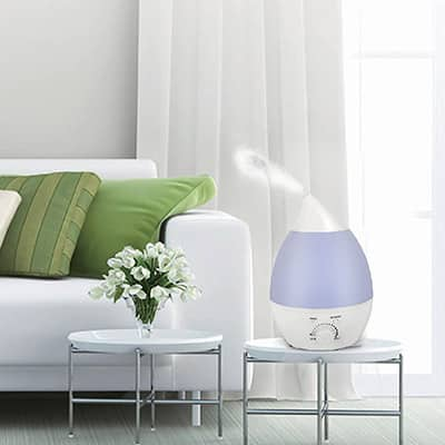 A humidifier on a glass table next to a sofa in a living room.