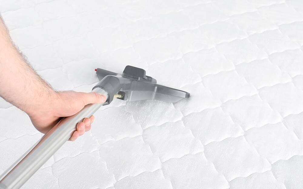 A person cleaning a mattress by vacuuming.