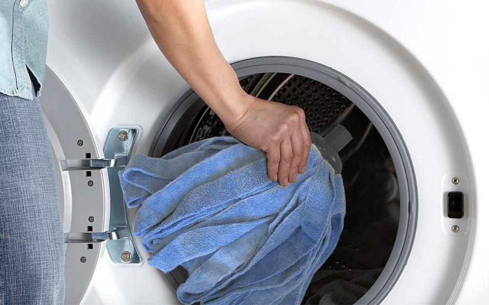 A person placing a microfiber cloth in a washer.