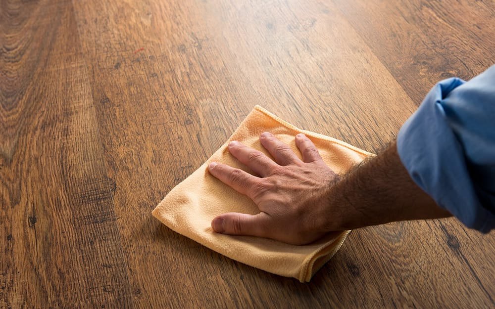 A person wiping a table with a microfiber cloth.