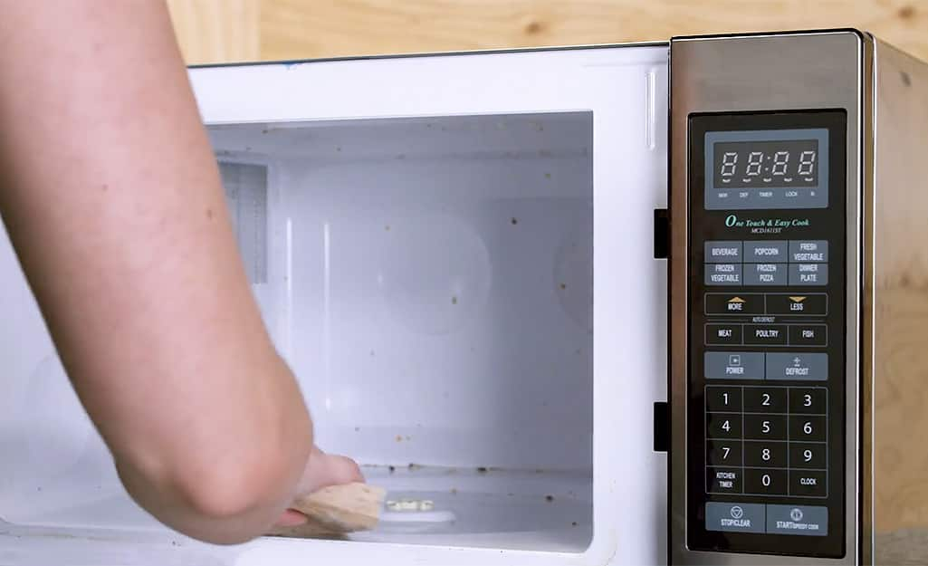 A woman wipes the interior of the microwave with a sponge.