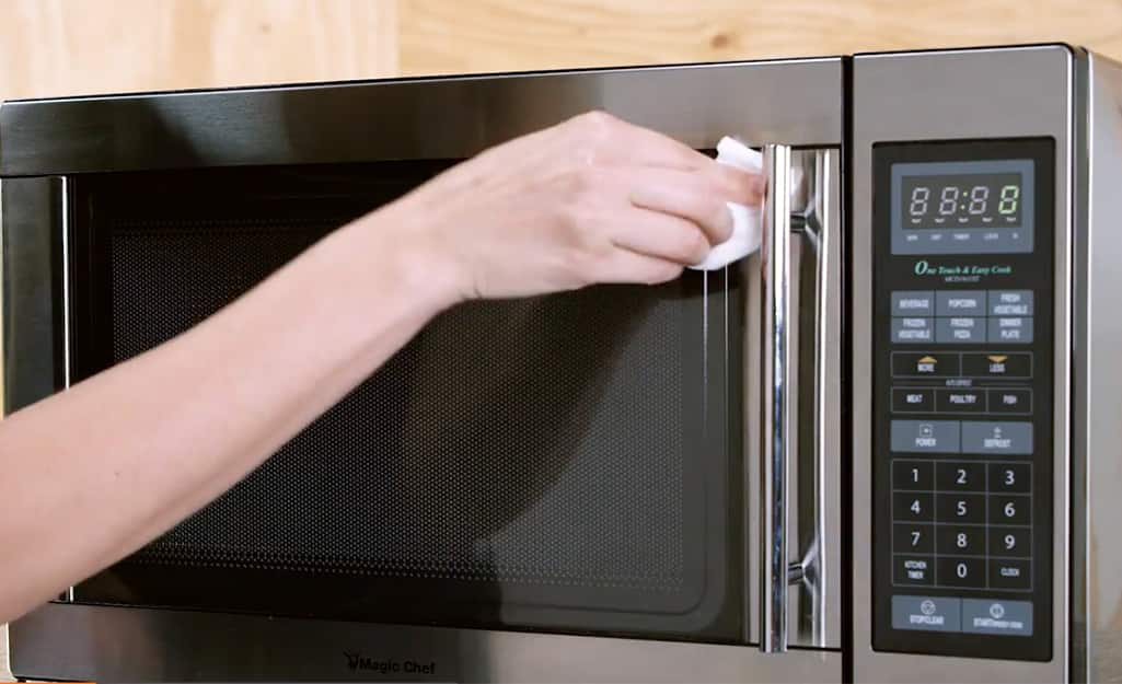 Woman wipes down the front door of a microwave with a paper towel.