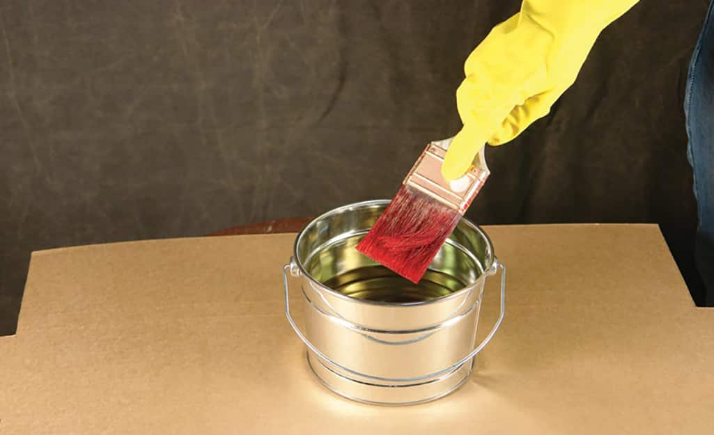 A person wearing kitchen gloves cleans a paint brush in a small container of solvent.