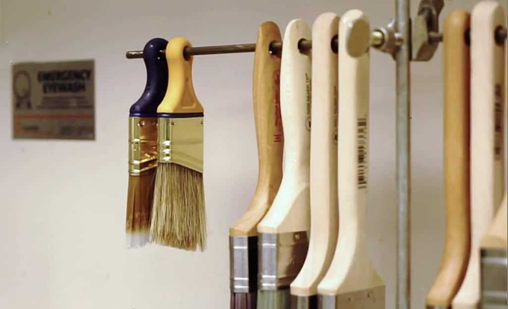 Paint brushes hang upside down from a metal rod.