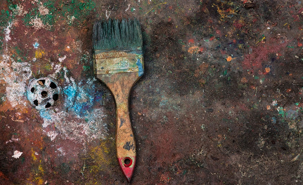 A paint brush with paint-hardened bristles lies near a drain.