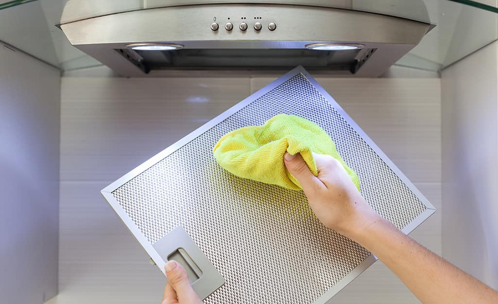 two hands cleaning a range hood filter with a cloth