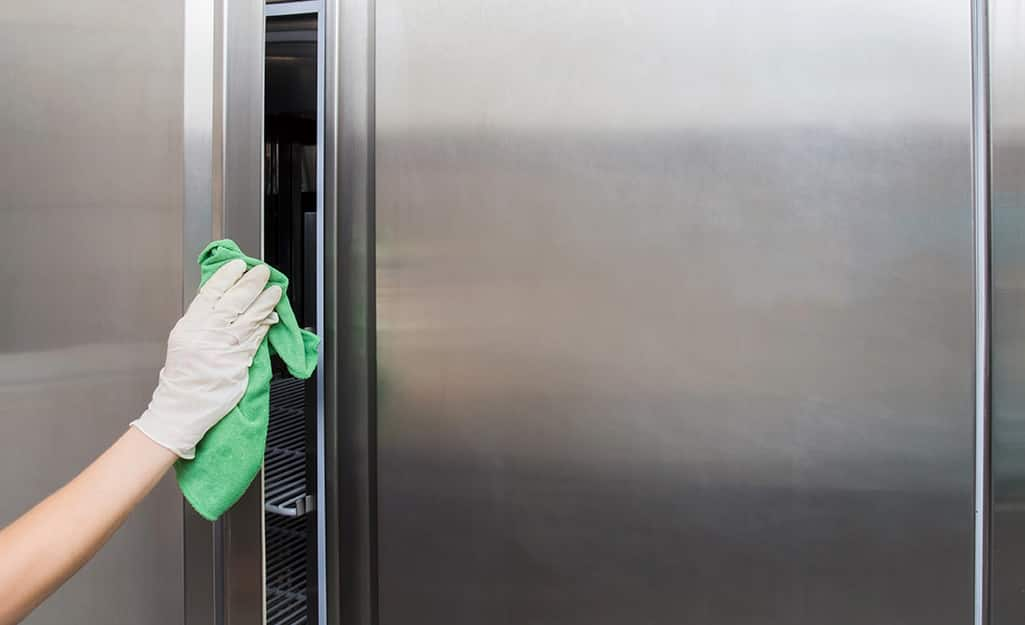 A person wears a glove and uses a cleaning cloth to wipe down the door handle of a refrigerator.