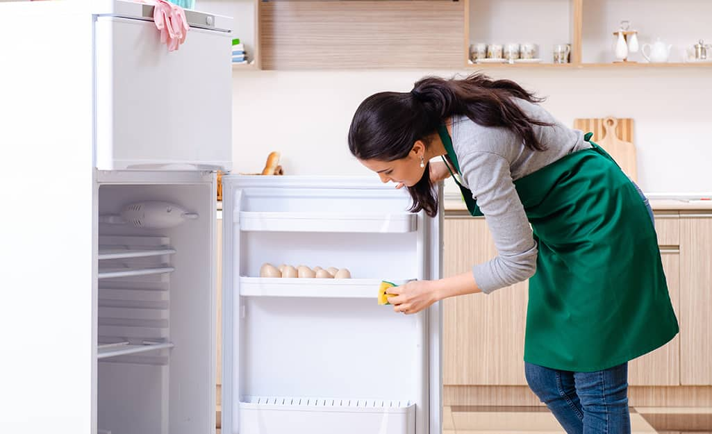 A person uses a sponge to wipe the interior door of a refrigerator.