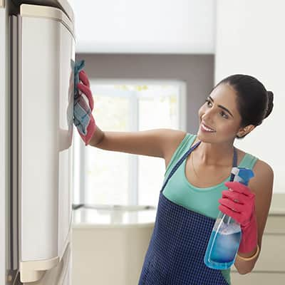 A person wears gloves to clean the door of a refrigerator with a cloth and a spray bottle.