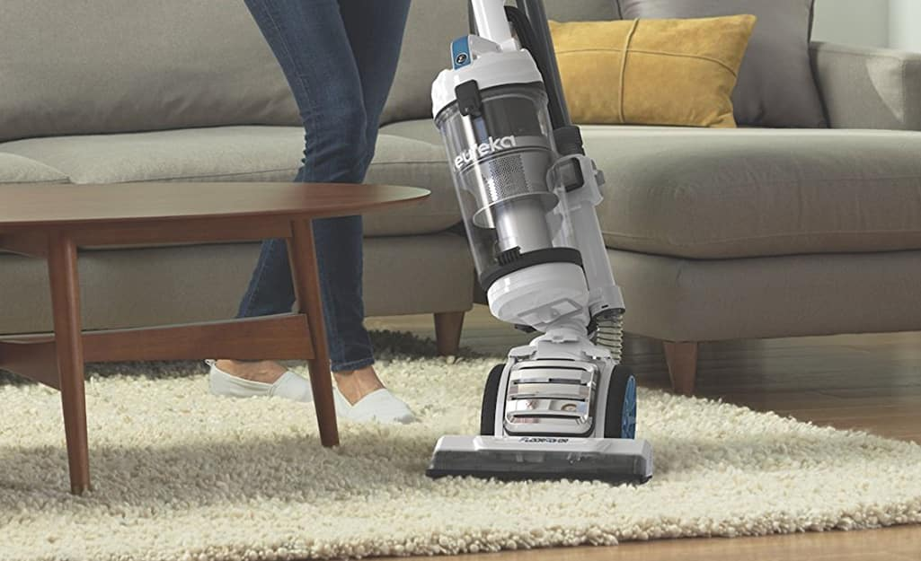 A person vacuuming an area rug.