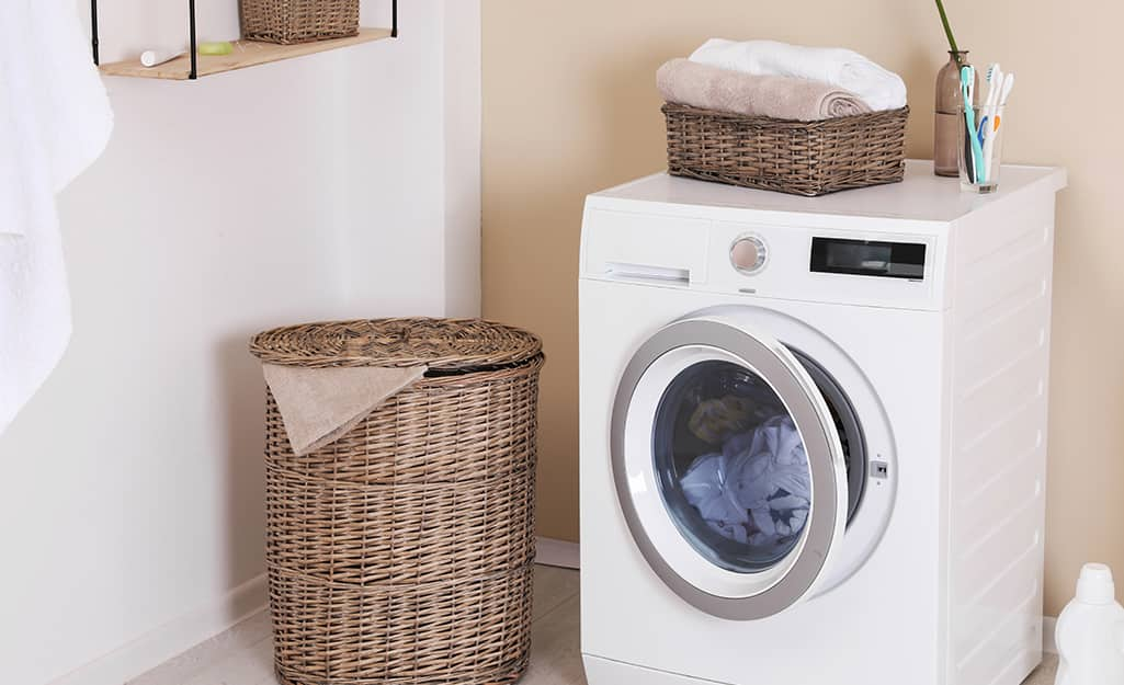 A white washing machine contains a load of white laundry in a laundry room.