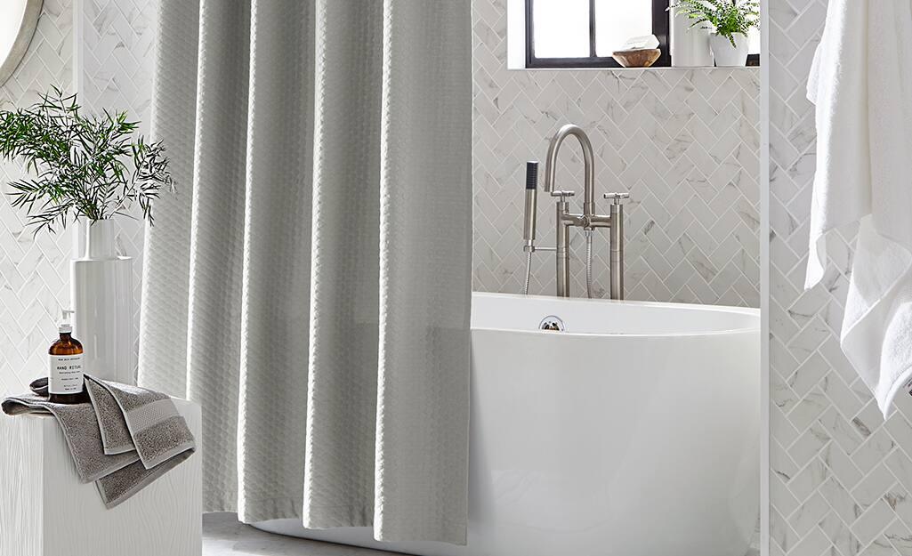 A gray shower curtain hangs outside a bathtub in a white bathroom.