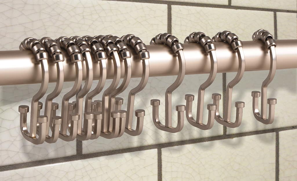 Shower curtain rings hang on a shower curtain rod in a bathroom.