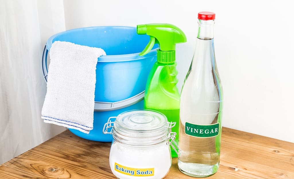 Vinegar, baking soda and a spray bottle stand next to a bucket for mixing a cleaning solution.