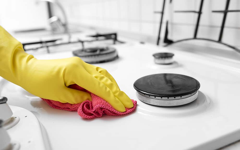 Someone wearing gloves using a cloth to wipe and clean a gas stove top.