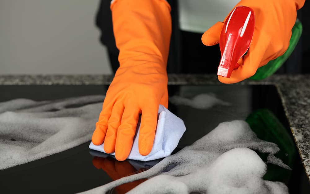Someone wearing gloves and cleaning a ceramic stove top.