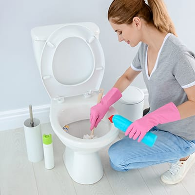 Woman cleaning a toilet wearing pink gloves.