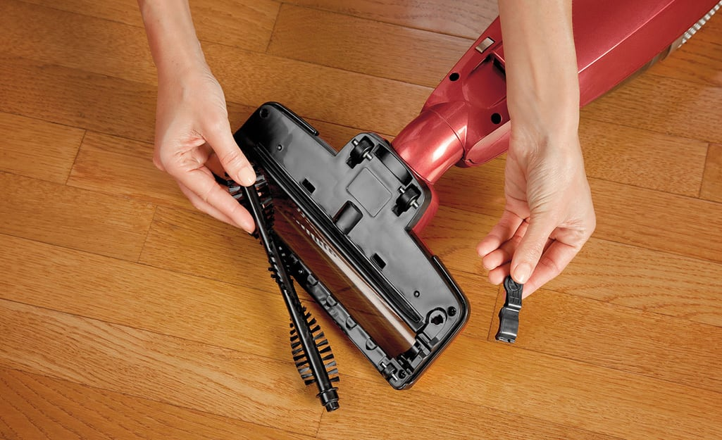 Someone taking a roller brush head off a vacuum cleaner.