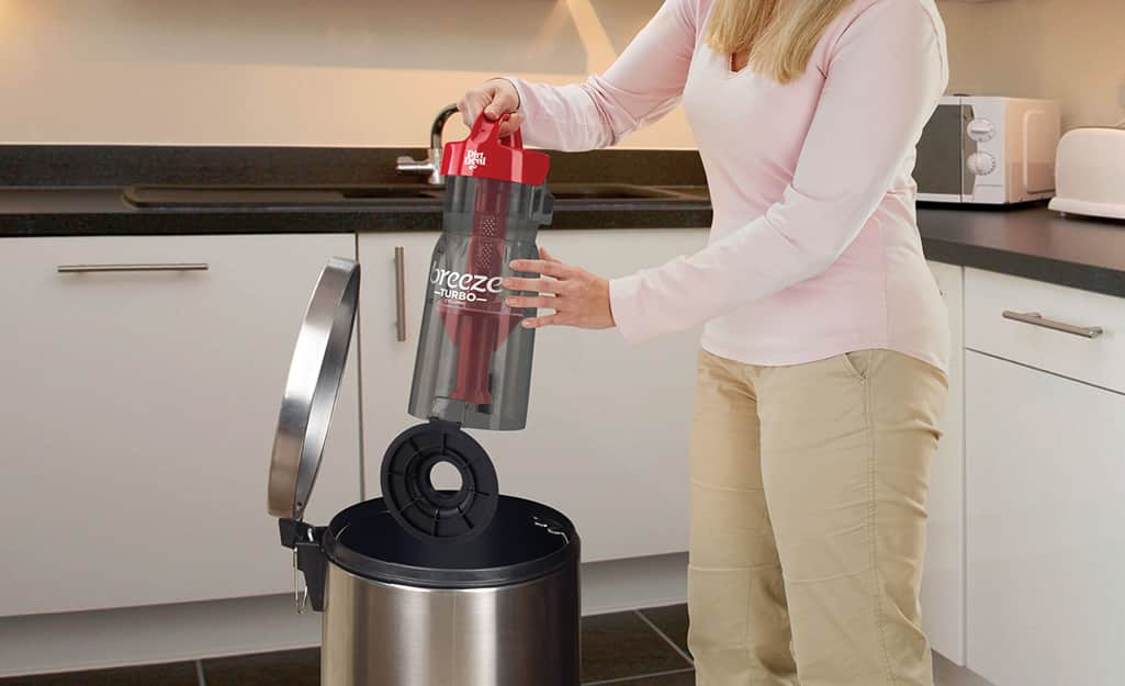 A woman emptying a vacuum cleaner canister into a trash can.