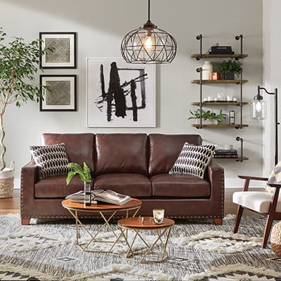 A brown leather sofa in a room with a wool area rug.