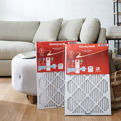 Two new air conditioner filters propped up near a couch.