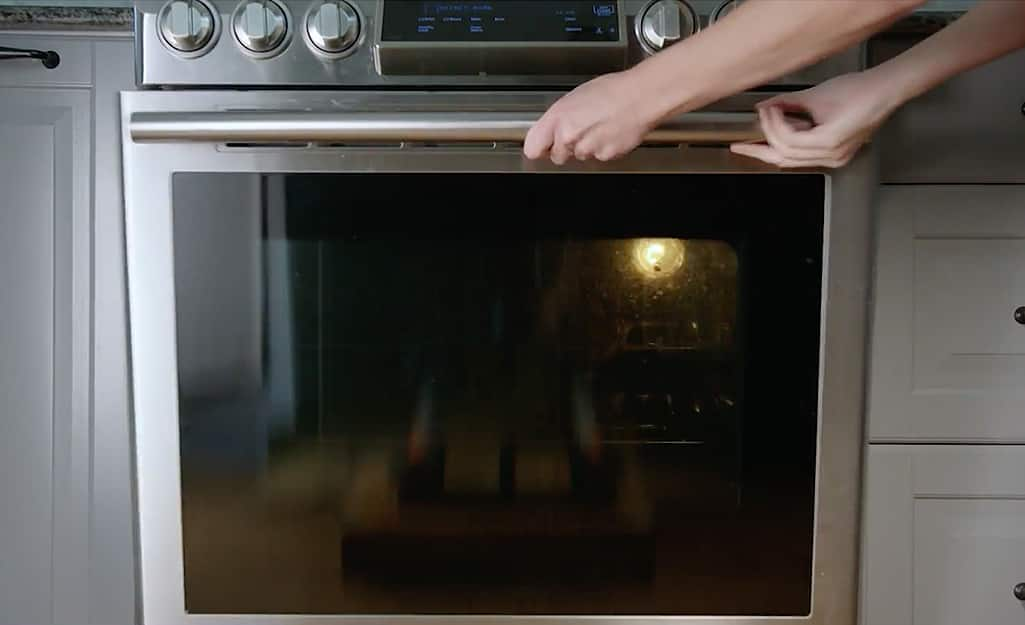 Someone opening a stainless steel oven door.
