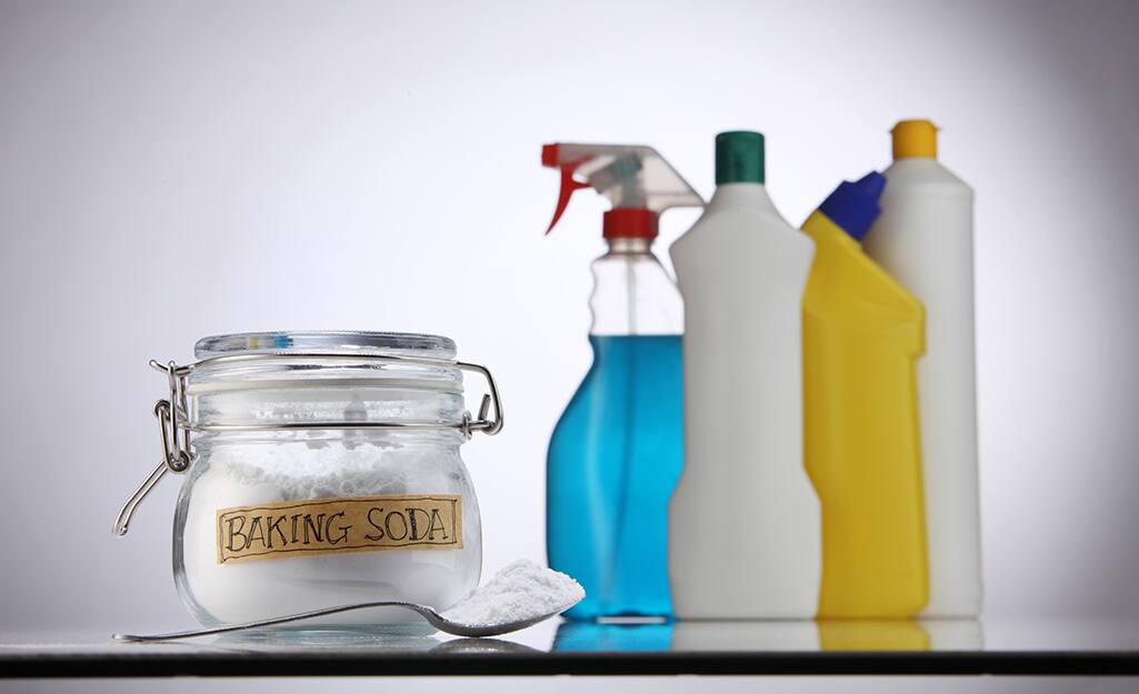 A glass jar of baking soda sitting next to other cleaning supplies.