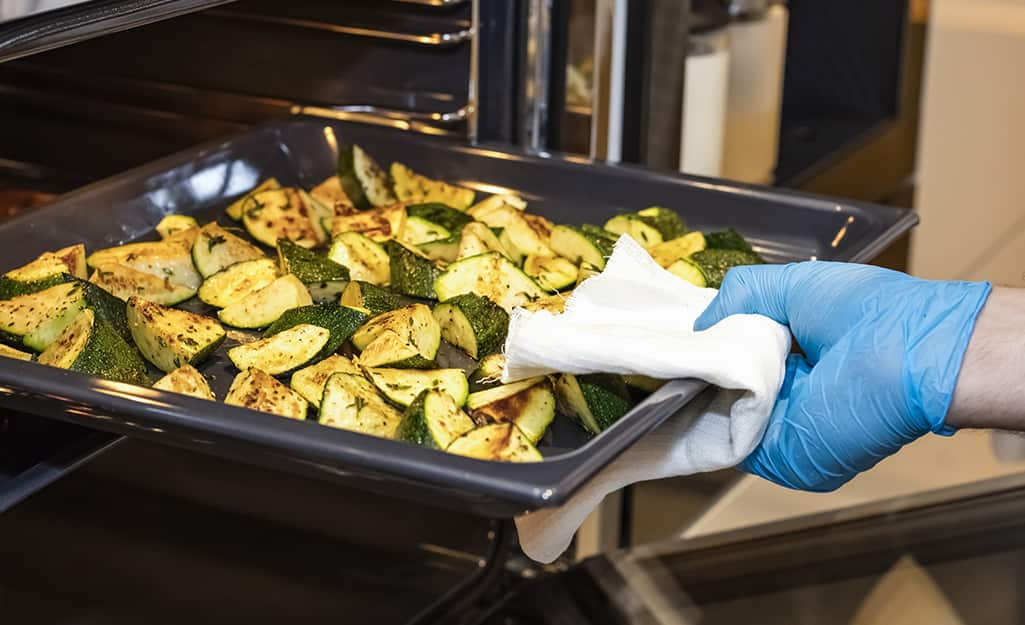 Someone pulling a pan of roasted vegetables from oven.