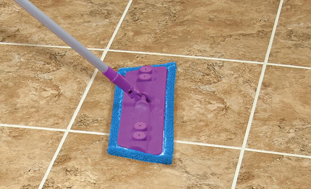 Someone using a mop to clean grout on a filed floor.