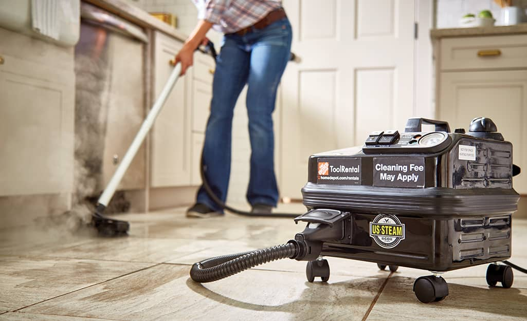 Someone using a steam cleaner to clean grout on a filed floor.