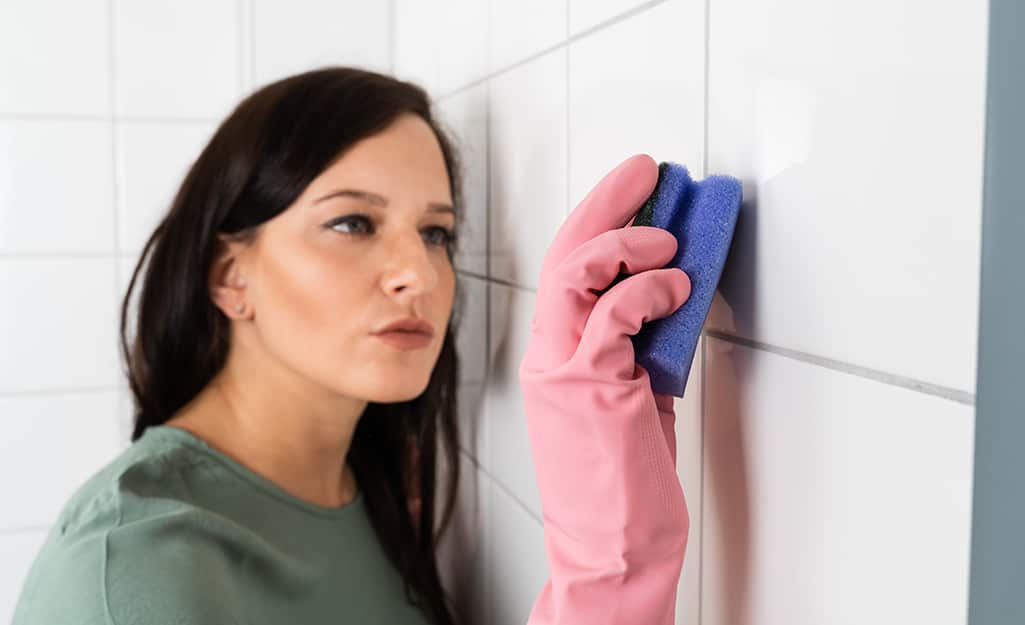 Someone using a scrubber to clean grout on a tiled wall.
