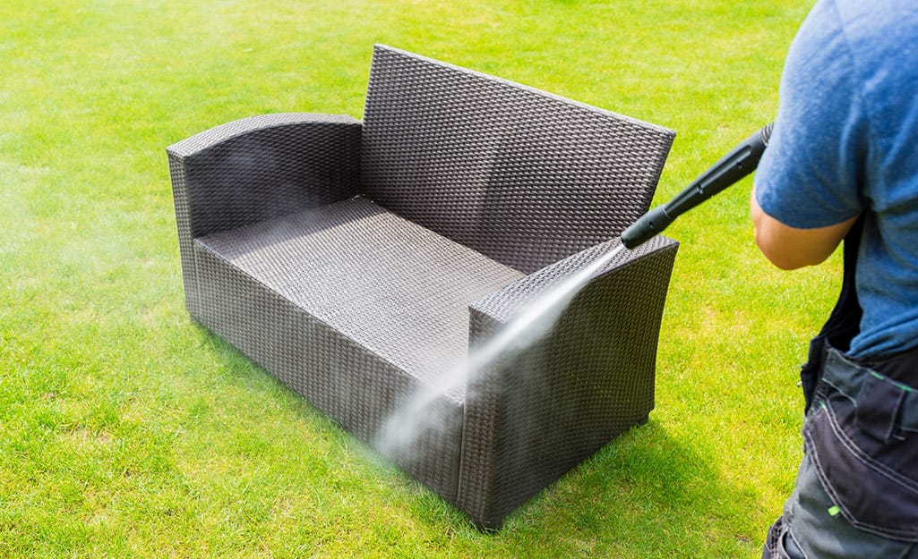 A person using a water hose to clean outdoor furniture.