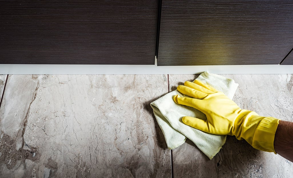 A person wearing kitchen gloves to clean a ceramic tile floor.