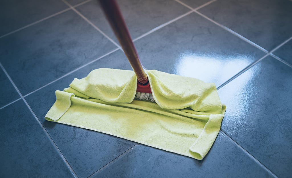 A person using a flat mop to clean a natural stone tile floor.