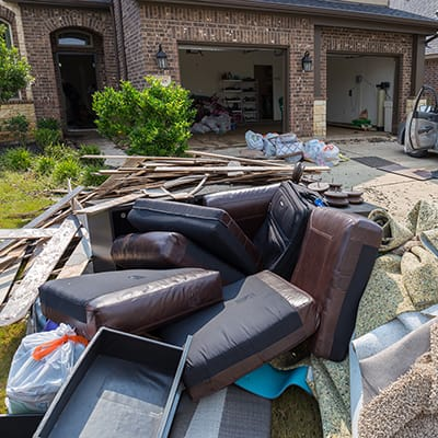 Discarded furniture and carpet outside a home after a flood.