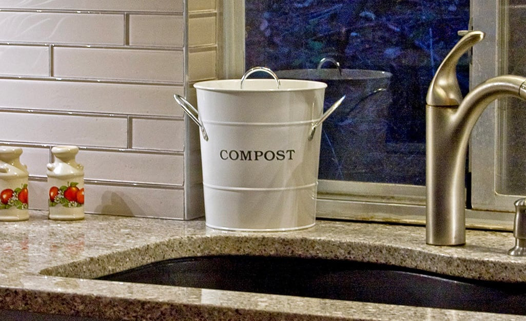 A compost pail sitting on a kitchen counter.