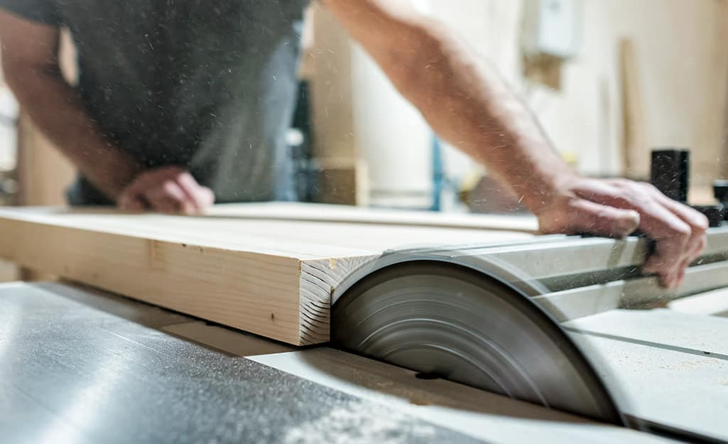 A worker trims wood board with a table saw.
