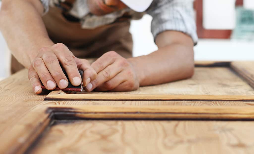 A worker installs the wood pattern on a door.