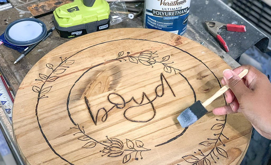A wood round is painted with sealant.