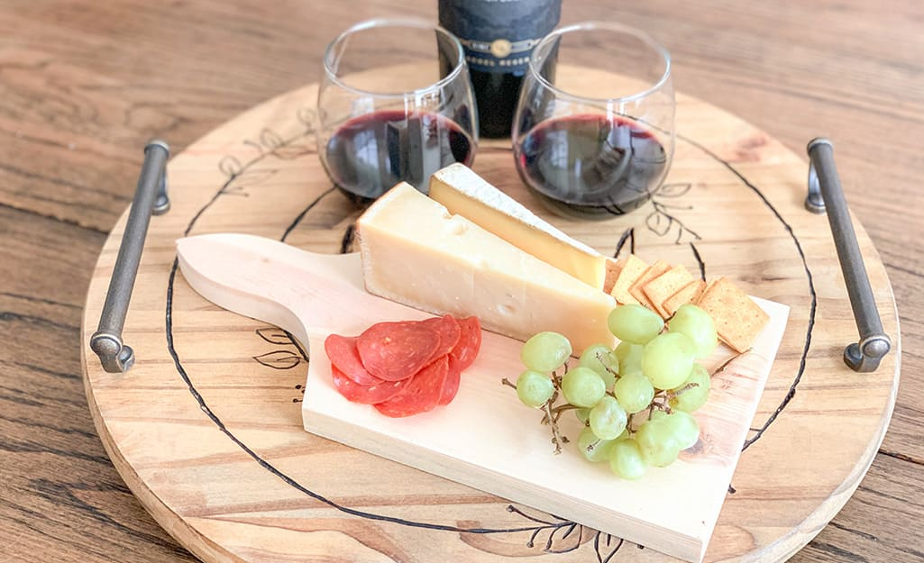 A finished Lazy Susan holds wine, cheese, fruit and meat.