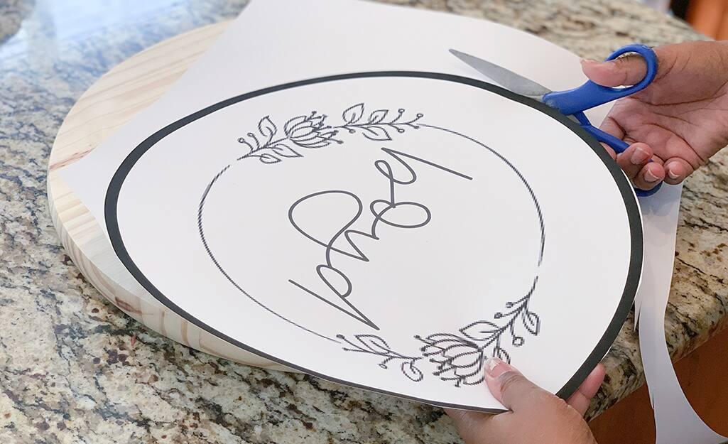 A person uses scissors to trim the design.