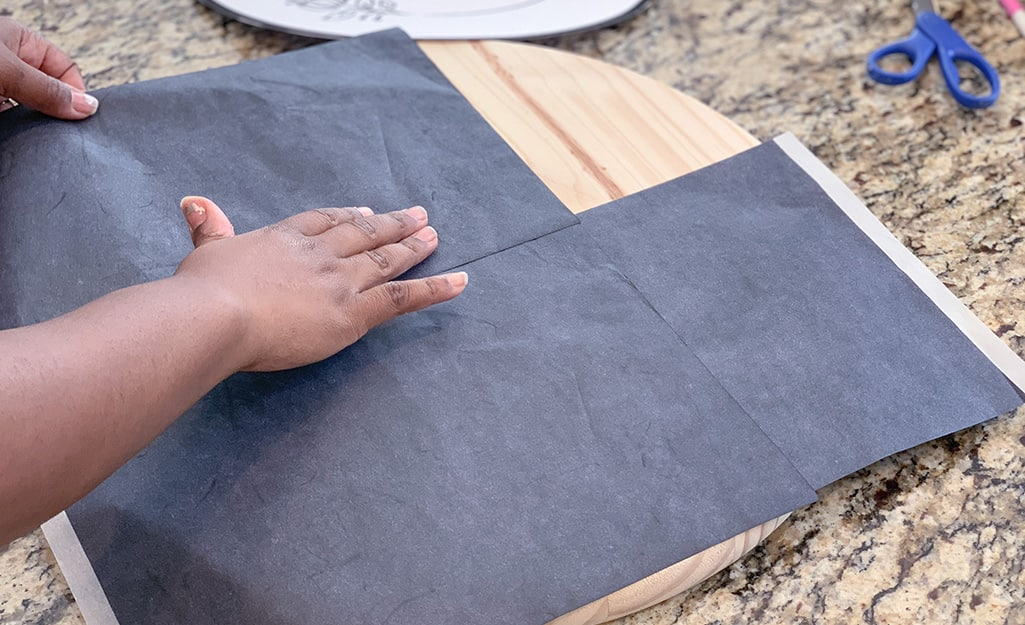 A woman lays carbon paper on top of a wood round.